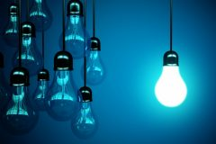 lampadina accesa su fondo blu